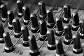 Black and white image of grand piano tuning pins