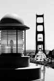 Black and white image of a light by the Golden Gate Bridge in San Francisco, California.