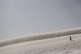 Little boy running in the sand dunes at White Sands National Monument in Alamogordo, New Mexico