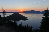 The sun rising over the Blue Crater Lake at Crater Lake National Park in Oregon.