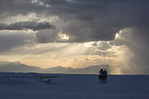 Three people capturing the sun rays fingering through the clouds at White Sands National Monument.