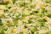 Cut brussel sprouds covered in shredded parmesan cheese with salt and pepper and olive oil.