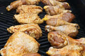 Basted and marinated chicken drumsticks and thighs grilling on the barbeque.