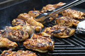 Chicken drumsticks and thighs grilling on the barbeque.
