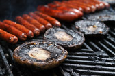 Hot dogs/franks and portabella mushroom caps grilling on the barbeque.