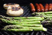 Asparagus, onions, and hot dogs/franks grilling on the barbeque.