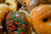 Variety of donuts includnig green and red sprinkles.