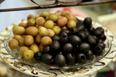Green and black olives on a plate.