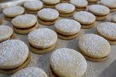 Alfajores cookies sandwiching dulce de leche sprinkled with powder sugar.