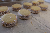 Homemade alfajores cookie sandwiches with finely shredded coconut on the ends that are covered with dulce de leche.