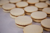 Alfajores cookies sandwiching dulce de leche waiting to be sprinkled with powdered sugar.