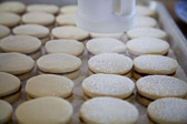 Alfajores cookies sandwiching dulce de leche being sprinkled with powder sugar.