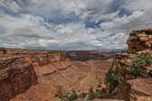 View of a rain falling in the distsance and a trail going through Canyonlands National Park in Utah.