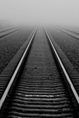 Black and white image of railroad tracks leading into the fog.