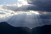 Sun rays streaming through the clouds onto Colorado mountains.