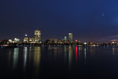 Skyline of Boston, Massachusetts at dusk with the moon party seen in the cloudy skies.