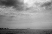 Rincon Island off the coast of Central California in black and white with light rays streaming through.