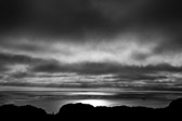 Sun shining through the clouds off the Pacific ocean coast of southern California in black and white.